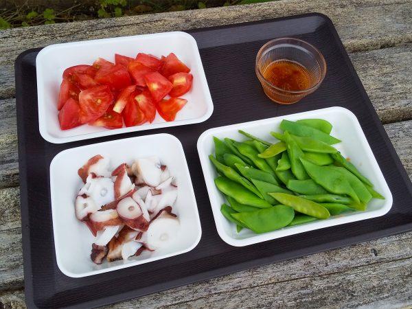 お刺身用の生食用たこスライスを食べやすい大きさにカットする。 モロッコいんげん、トマトも食べやすい大きさに。 トウモロコシは包丁で身を落としておく。(コーンの缶詰でも可)