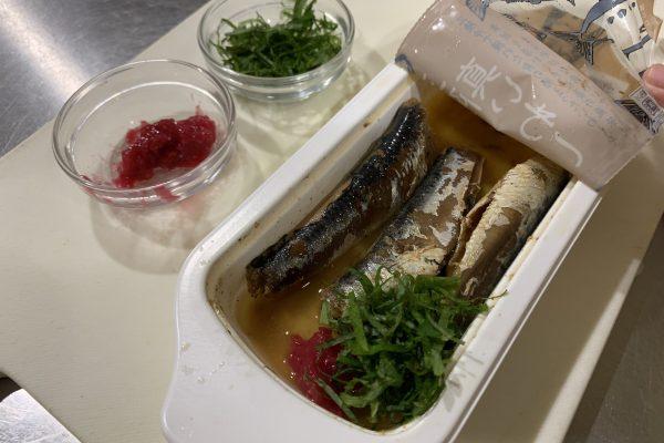 「魚やの煮付 三陸真いわし」のトレーを開け、先ほどの梅干しと大葉を入れて、電子レンジで30秒温めます。