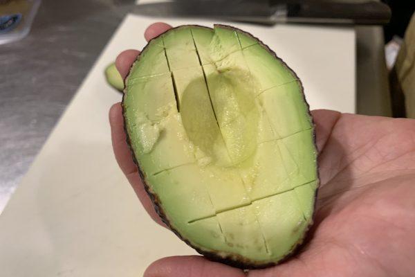 アボカドを半分に切り、タネをとり、このように格子状に包丁を入れます。