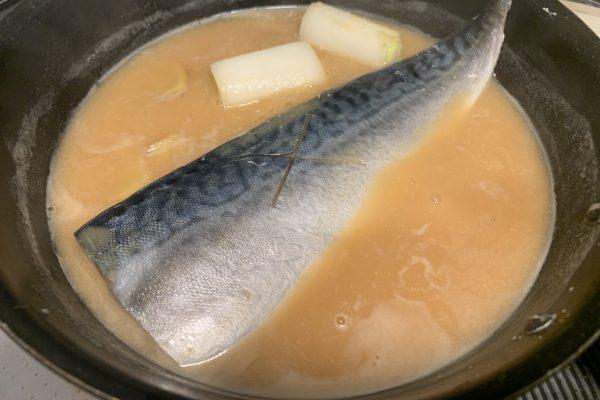 鯖のフィレを入れ、酒を鯖にかけるように入れます。
