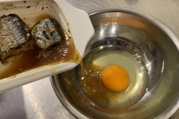 さんまの煮付のトレーを少しあけ、電子レンジで30秒ほど温めたあと、汁のみを卵に入れ